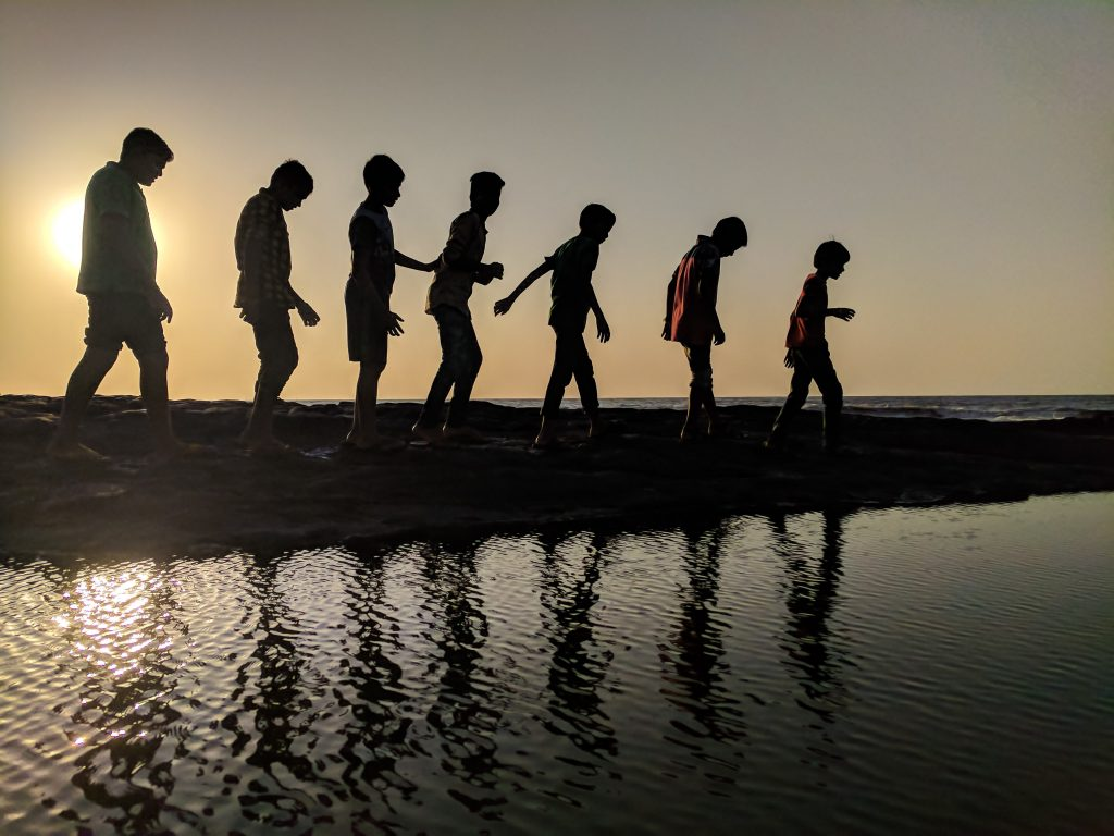 group-of-children-walking-near-body-of-water-silhouette-939700